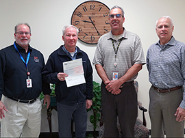 Austin Energy representative hands a check to LTISD facilities personnel
